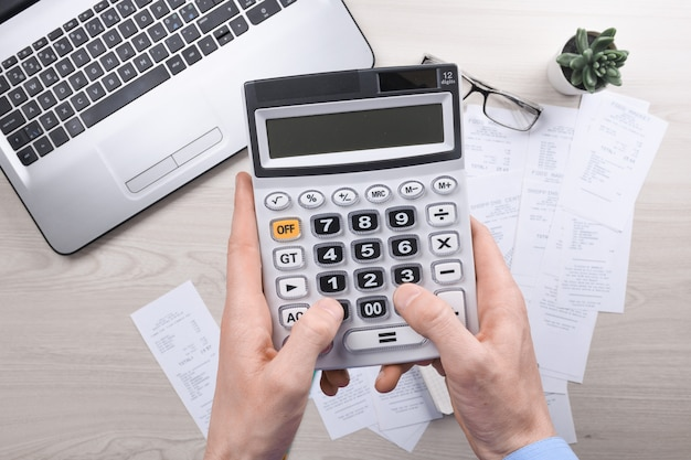 Unrecognizable businessman using calculator on desk office and writing make note with calculate about cost at home office.
