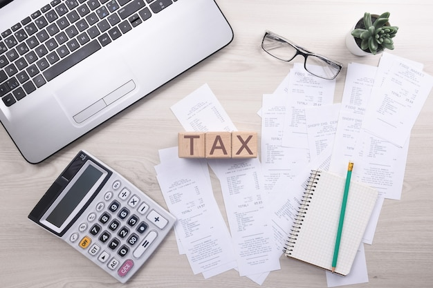 デスクオフィスで電卓を使用して書き込みをしている認識できないビジネスマンは、ホームオフィスでのコストについて計算してメモします。財務会計の概念。税金、買い物、コスト管理。