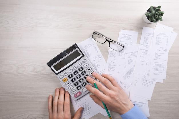 Непознаваемый бизнесмен используя калькулятор на офисе стола и писать делает примечание с высчитывает о стоимости дома офисе.