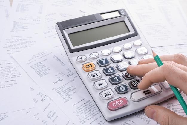 Неузнаваемый бизнесмен, использующий калькулятор на столе в офисе и записывающий, делает заметку с расчетом стоимости в домашнем офисе