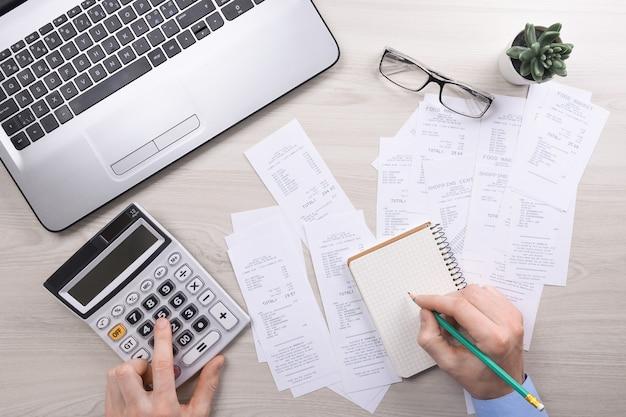 До неузнаваемости бизнесмен, использующий калькулятор на столе в офисе и записывающий, делает заметку с расчетом стоимости в домашнем офисе