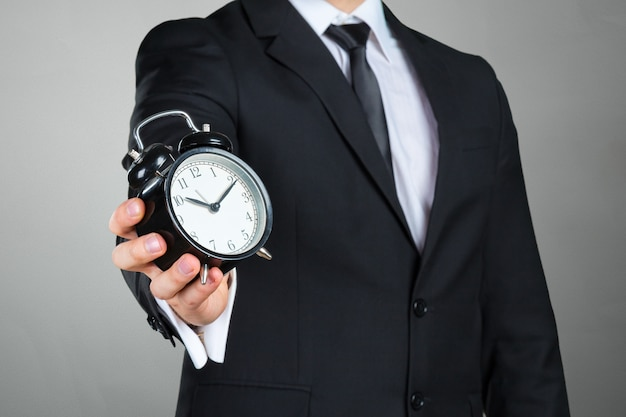 Unrecognizable businessman with an alarm clock in a hand