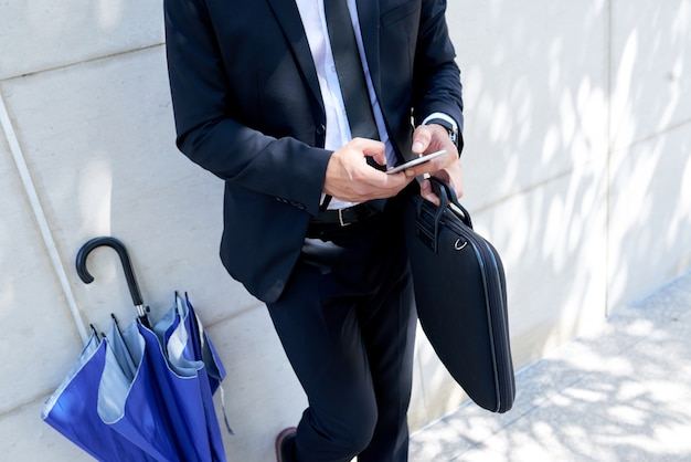 Unrecognizable businessman with briefcase and umbrella standing outdoors and using smartphone