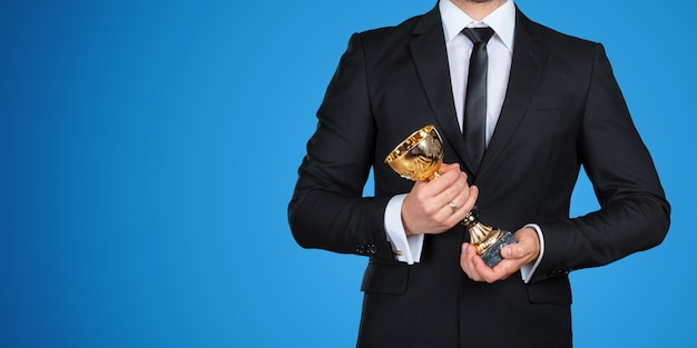 Unrecognizable businessman with a golden trophy. success concept
