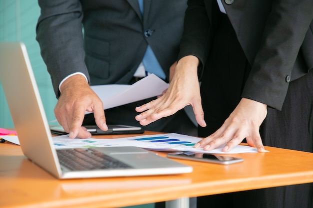 Unrecognizable businesspeople studying statistics and holding papers with hands