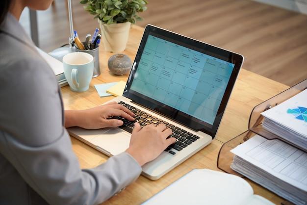 Donna di affari irriconoscibile che si siede allo scrittorio con il computer portatile e che esamina calendario
