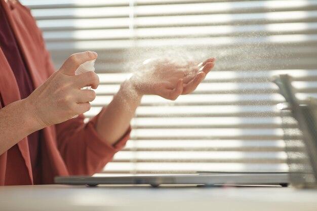 До неузнаваемости бизнесвумен опрыскивает руки дезинфицирующим средством на рабочем месте
