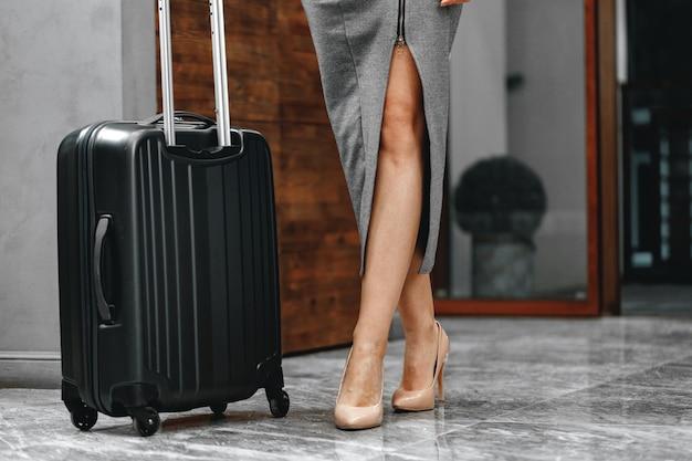 旅行かばんのクローズアップ写真で立っている認識できない実業家