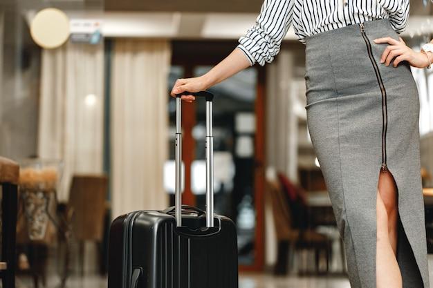 旅行かばんを持って立っている認識できない実業家