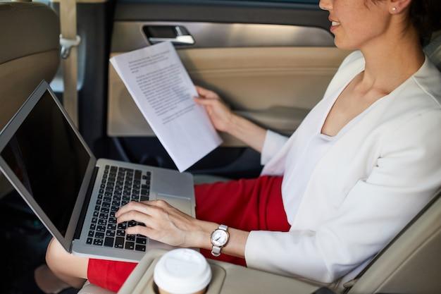 Unrecognizable businesswoman working in car