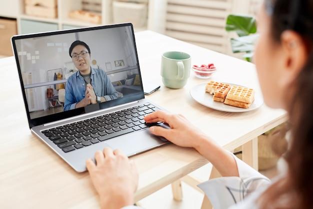 그녀의 노트북에서 온라인 기술을 사용하여 아시아 남자와 일하는 인식 할 수없는 사업가