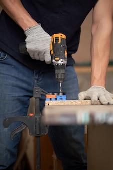 До неузнаваемости плотник в белых перчатках со сверлом и доской в мастерской