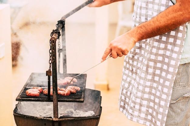 인식 할 수없는 백인 성인 수석 남자 요리와. 오래된 전통적인 불로 고기를 준비하십시오. 야외 정원에서 집에서 바베큐 그릴