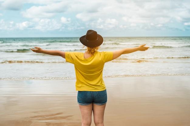До неузнаваемости кавказская женщина с распростертыми объятиями на пляже в солнечный день концепции свободы