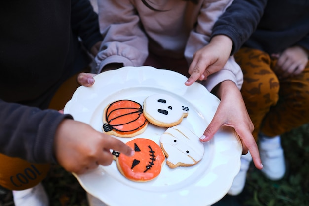 Unrecognizable children hold plate of homemade cookies decorated for halloween