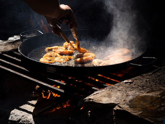 Unrecognizable cooker flipping shrimps roasting on pan with tongs