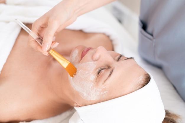 Неузнаваемый косметолог наносит маску для лица с кисточкой зрелой женщине на косметической процедуре