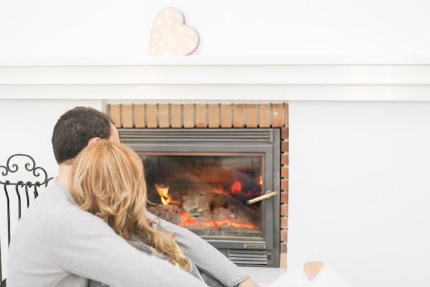 Unrecognizable couple near fireplace