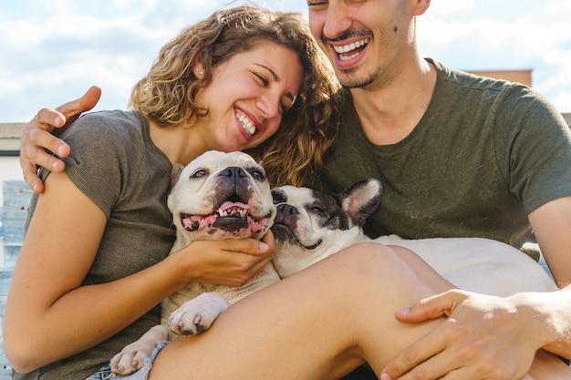 집에서 강아지와 놀고 있는 알아볼 수 없는 커플. 소파에 불독과 함께 웃고 있는 커플의 가로 보기.