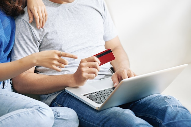 Unrecognizable couple sitting on couch with laptop and man holding credit card