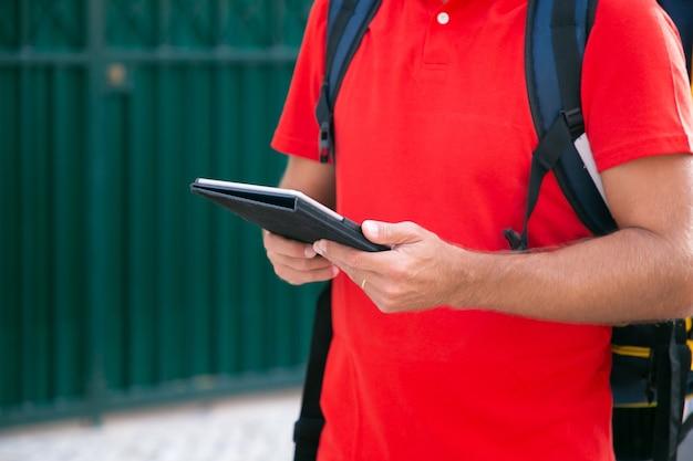 タブレットを手に持って立っている認識できない宅配便。サーマルバックパックで注文を配達し、赤いシャツを着ている配達員のトリミングされたビュー。配送サービスとオンラインショッピングのコンセプト