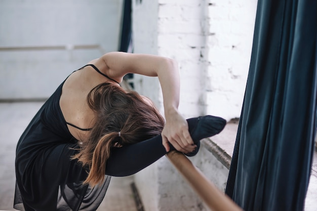 Unrecognizable dancer exercising near barre