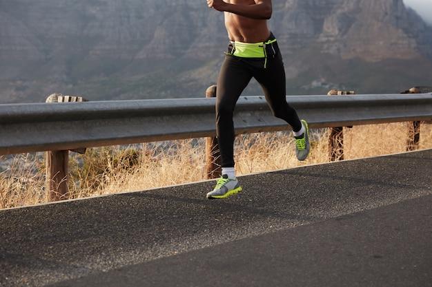 Il corridore veloce dell'uomo dalla pelle scura irriconoscibile sprint all'esterno, corre nel paesaggio naturale, conduce uno stile di vita sano, indossa scarpe sportive comode. concetto di esercizio sportivo. immagine con copia spazio