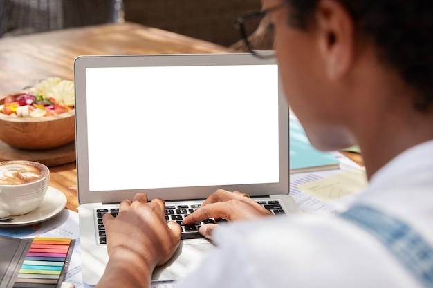 광고 콘텐츠를위한 빈 화면 영역이있는 랩톱 컴퓨터에서 인식 할 수없는 어두운 피부 여성 키보드