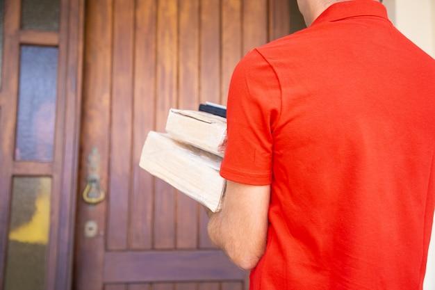 段ボール箱を持ってドアに行く認識できない配達員。自宅で注文を配信する赤いシャツの宅配便の背面図。速達サービスとオンラインショッピングのコンセプト