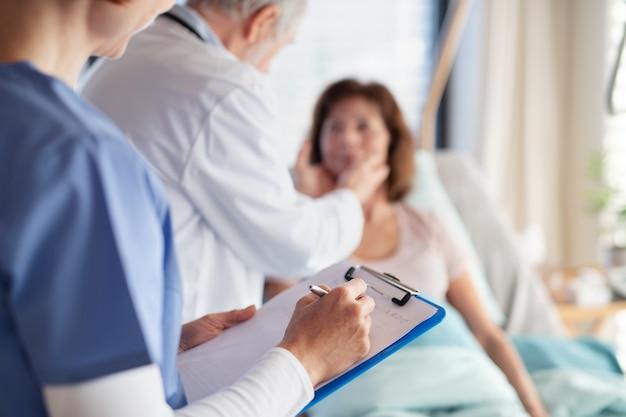 病院の中央部で女性患者を診察している認識できない医師と看護師。
