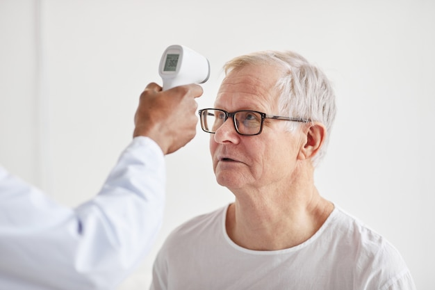 Unrecognizable doctor checking temperature of patient in hospital and pointing infrared thermometer on senior man