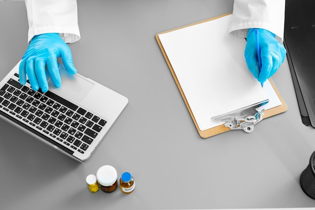 그의 작업 테이블에 앉아있는 동안 메모를 만드는 장갑에 인식 할 수없는 의사가 닫습니다.