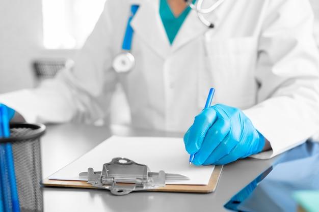 До неузнаваемости доктор в перчатках делает заметки, сидя за своим рабочим столом крупным планом