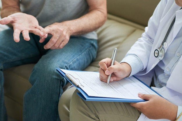 Unrecognizable doctor talking to patient at home and making notes
