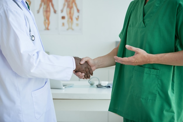 Unrecognizable doctors greeting each other shaking hands