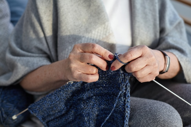 Unrecognizable elderly senior woman wearing wide gray scarf and wrist watch, knitting sweater. close up view of aged female hands holding needles and yarn, doing needlework. selective focus