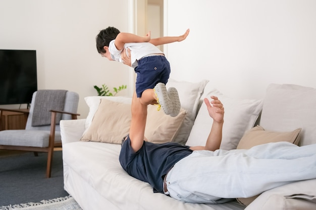 Unrecognizable father lying on couch and holding son on one hand.