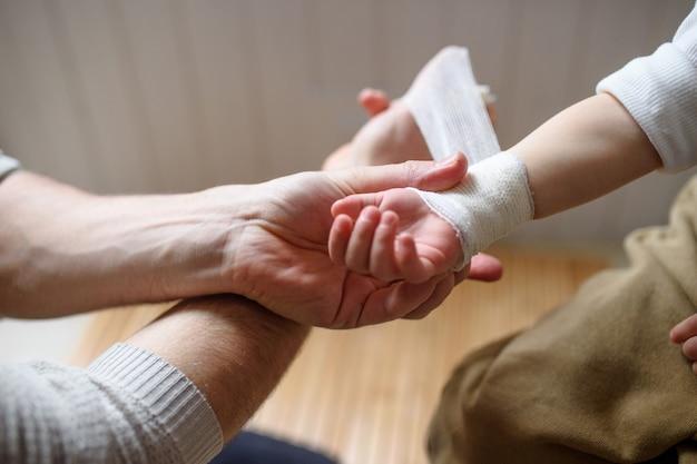 家の屋内で小さな傷ついた幼児の子供に包帯を巻いている認識できない父親。
