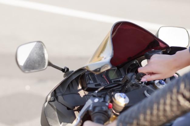 Непознаваемая женщина-байкер включает двигатель мотоцикла