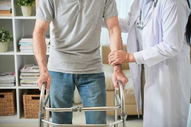 Unrecognizable female doctor helping male patient walk with walking frame