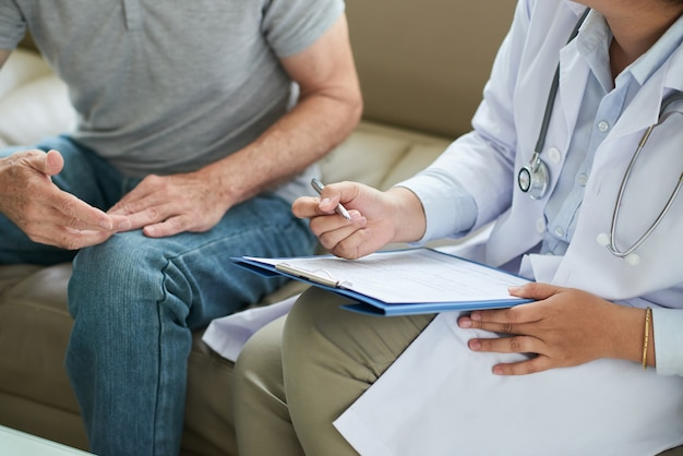 Unrecognizable female doctor sitting on couch with male patient and filling form