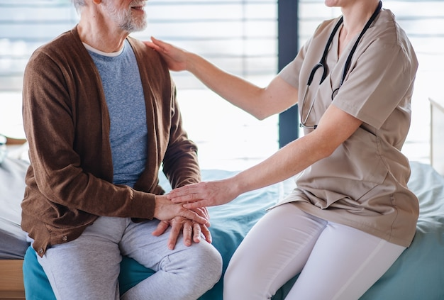 病院の中央部のベッドで年配の患者と話している認識できない女性医師。