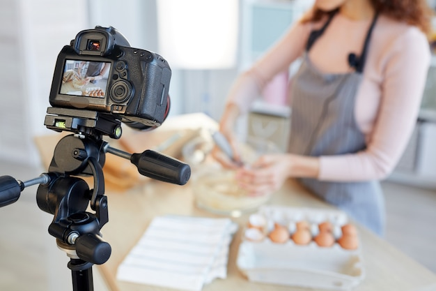 Unrecognizable female food blogger cooking bakery dough on camera, horizontal shot