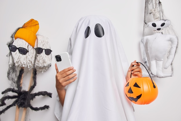 Unrecognizable female ghost holds modern mobile phone and carved pumpkin prepates for halloween celebration searches in internet ideas to decorate room before party poses near scary toys indoor.