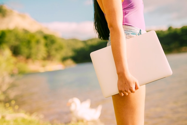 Unrecognizable female holding laptop in picturesque place