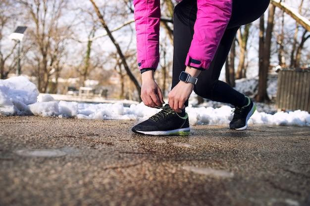 겨울에 공원에서 신발 끈을 묶는 스포츠 장비에서 인식 할 수없는 여성.