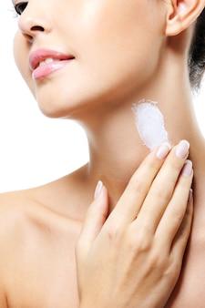인식 할 수없는 여성 사람이 목에 화장품 크림을 바릅니다.