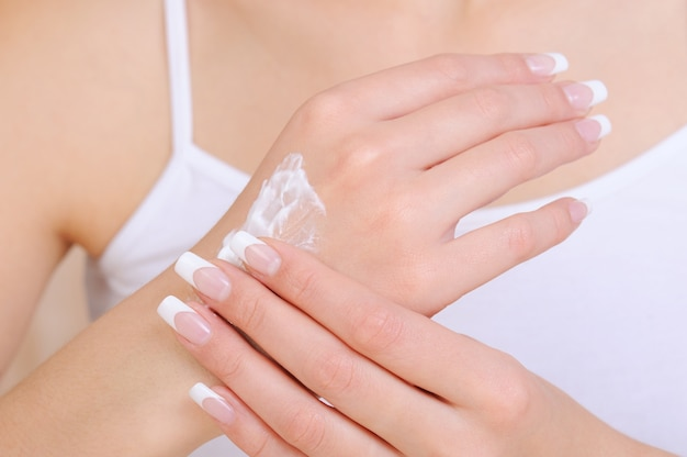 Unrecognizable female person applying cosmetic moisturizing   cream on hand