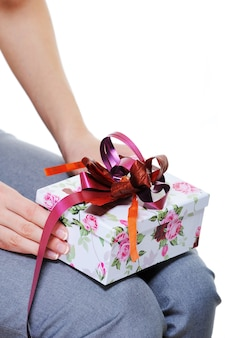 Unrecognizable female person holding on her knees  present box