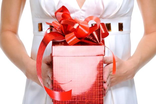 До неузнаваемости лицо женского пола, держащее красную подарочную коробку - изолированное на белом